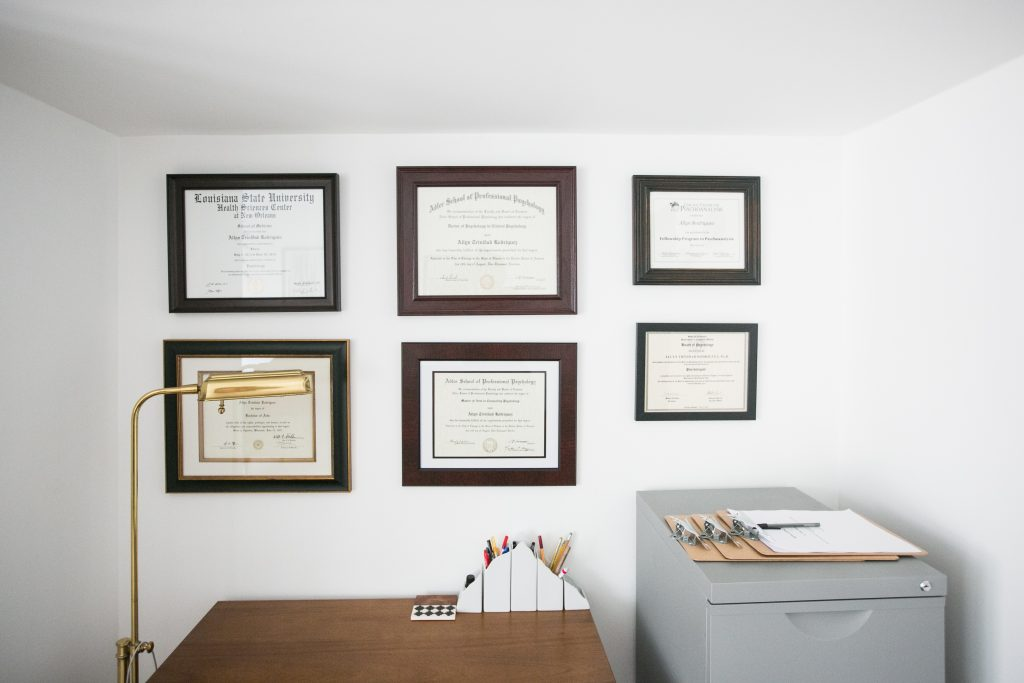 Picture of desk, lamp, and diplomas hanging on wall